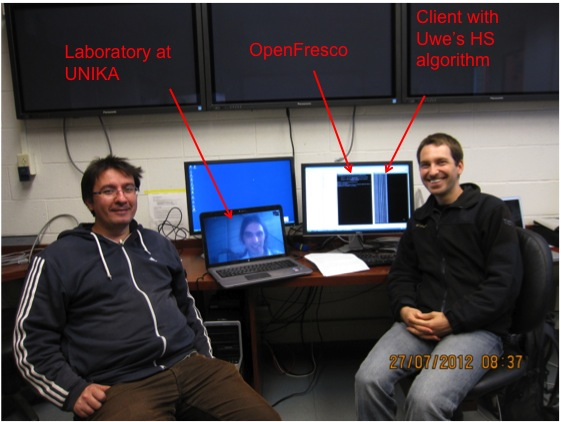 The testing team of Andreas Schellenberg and Selim Gunnay at UC Berkeley's nees@berkeley laboratory, pose for a photo with Professor Uwe Dorka who is virtually present from the civil engineering laboratory at the University of Kassel (UNIKA) in Germany.